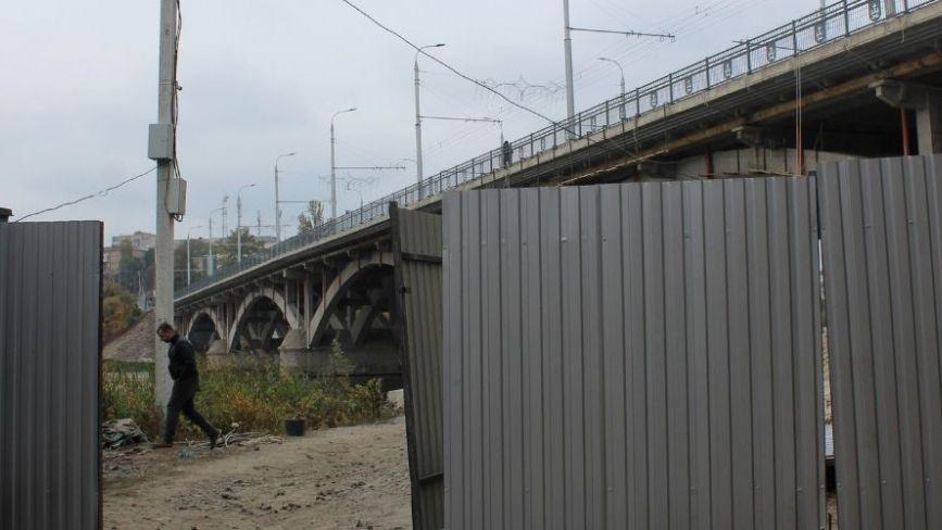 Поставили паркан і повісили риштування. Що відбувається під Київським мостом?