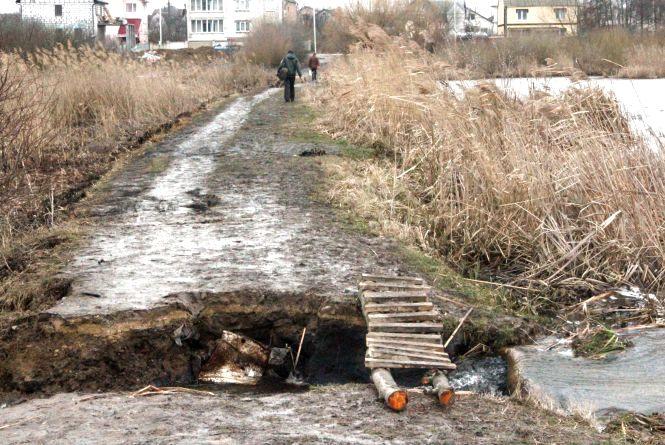 """На  ставку """"Качатник"""" люди переходять по містку. Трубу ще не встановили"""
