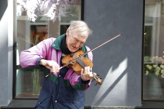 Прикутий до скриньки з грошима незрячий скрипаль грає біля Вежі (ВІДЕО ДНЯ)