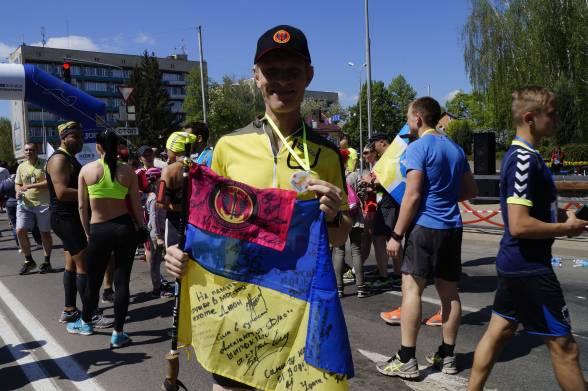 Житомирянин Віктор Юрченко пробіг 21 кілометр за 1 годину 34 хвилини. Приїхав з друзями та дочкою. Демобілізувався в серпні 2016 року, з того часу у бере участь у забігах. На прапорі слова від побратимів з 36-ї бригади морської піхоти
